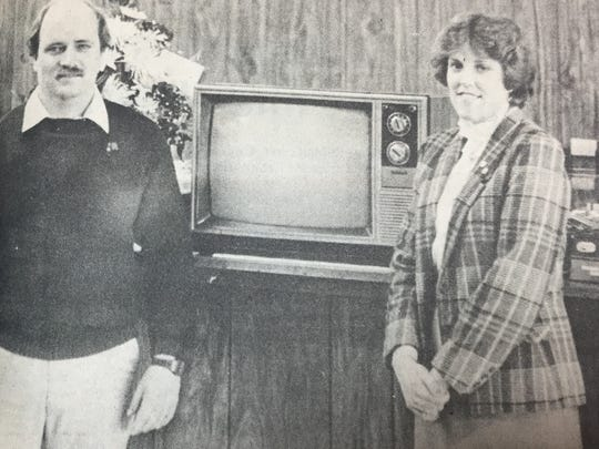 John Roetteger, left, president of J.R. Chevrolet-Pontiac Inc., stands with a 19 inch color television awarded to Ms. Judy Amiet, right. The television was the grand prize during the dealership's Grand Opening in March 1984.