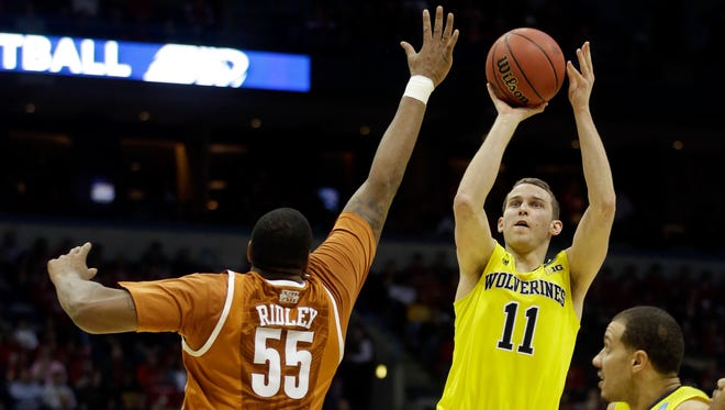 Michigan guard Nik Stauskas (11) takes a shot against Texas center Cameron Ridley (55) during the first half of a third-round game of the NCAA Tournament on March 22, 2014, in Milwaukee.