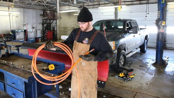 """T.J. Schouten of Dallas Center, Iowa, finishes up maintenance on his pickup at the DIY Garage. """"I like to do a lot of the work myself if I can,"""" he says."""