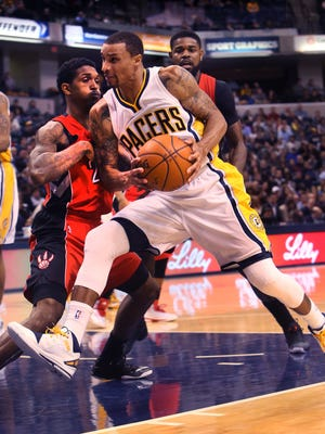 Indiana Pacer George Hill tries to muscle his way in the lane against Toronto Raptor Lou Williams (left) but lost his grip on the ball. The Pacers turned the ball over and lost to the Raptors, 104-91, at Bankers Life Fieldhouse in Indianapolis on Tuesday, Jan. 27, 2015.