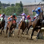 Tori Gandia, in the number 3 silks, pushes Rio Good ahead of Zachary Bacon, riding Maker Happen Captain, during the third race on opening day at the 2015 State Fair Race Meet at Montana ExpoPark.