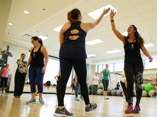 Sarah Katerle high fives her Zumba coach, Lisa Bongard, at the Eastside YMCA during a work out. Sarah's lost 100 pounds by working out and eating healthy and credits Lisa for supporting her through her goals.