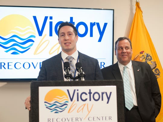 A.J. Solomon, a former Christie staffer and recovering heroin addict, speaks during the opening of Victory Bay Recovery Center in Laurel Springs recently as Gov. Chris Christie looks on.