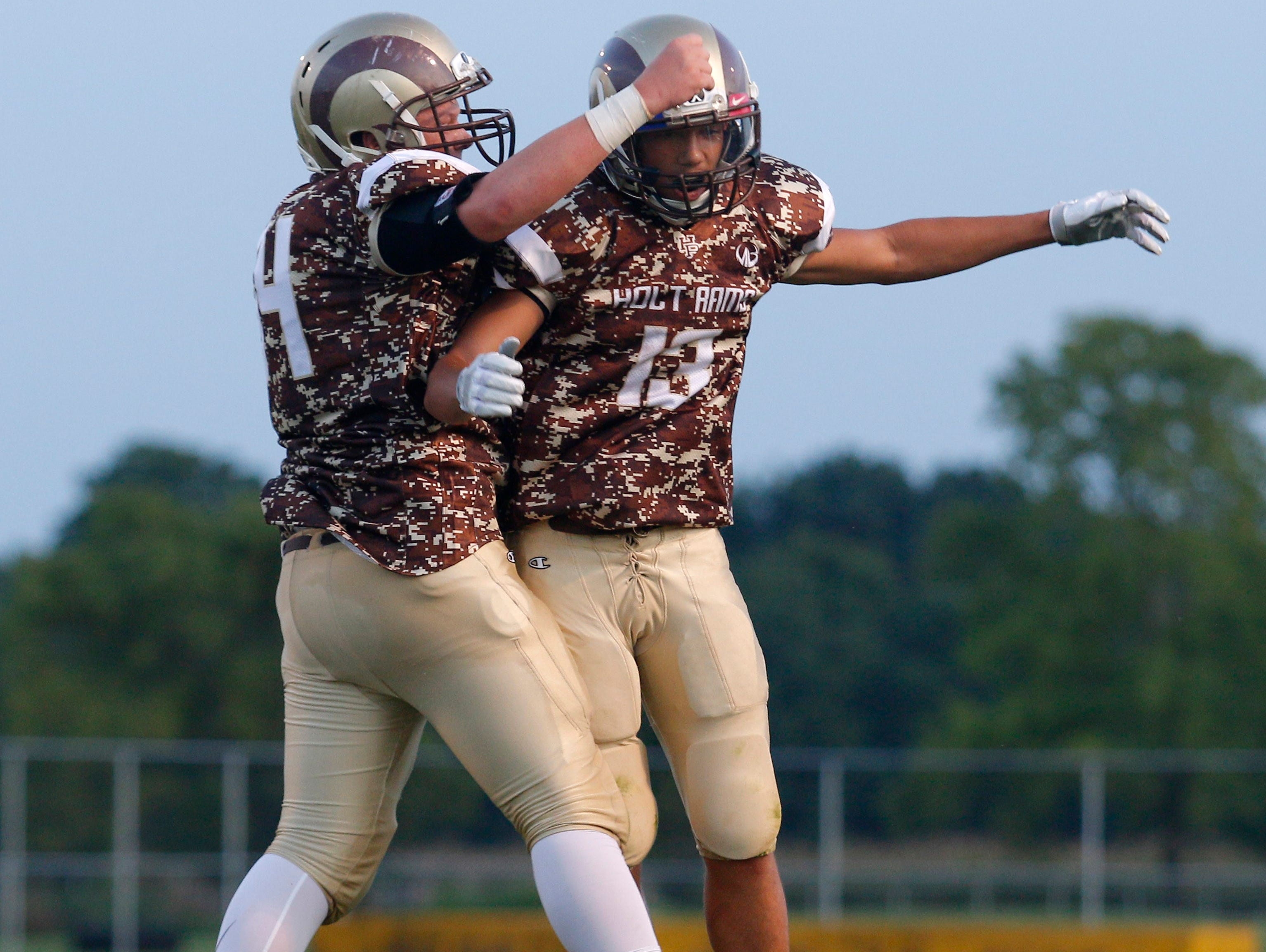 Holt's Troy Jordan, right, and Mitch Johnson celebrate Jordan's touchdown against Lansing Everett Friday, Sept. 16, 2016, in Holt, Mich.