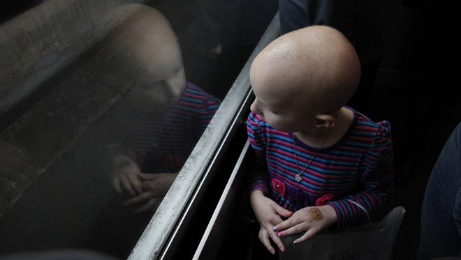 Amanda Conrow looks out from the parking garage elevator on her way out of Strong Memorial Hospital after one of her many treatments for ependymoma.