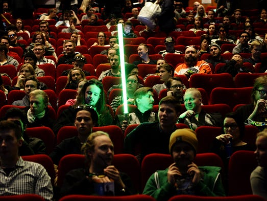 A Star Wars fan waits with his mock light sabre for
