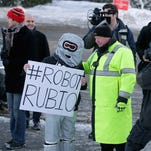A police officer tells an anti-Marco Rubio demonstrator dressed as a robot not to block the sidewalk outside the polling place Tuesday at Webster School in Manchester, N.H.