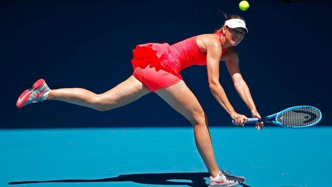 Russia's Maria Sharapova makes a backhand return to Croatia's Donna Vekic during their first round singles match at the Australian Open tennis championship in Melbourne, Australia, Tuesday, Jan. 21, 2020.