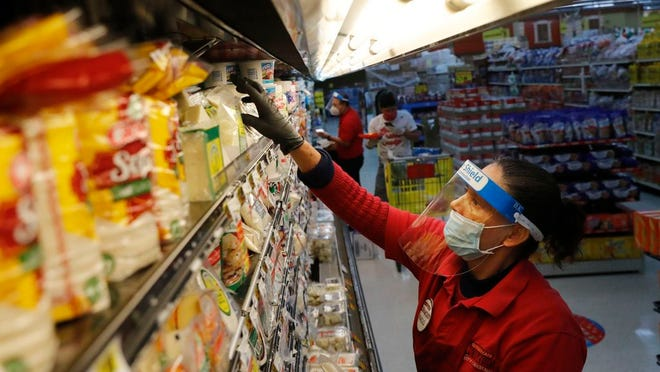 Maclola Orozco wears protective gear as a precaution against the coronavirus as she restocks shelves at El Rancho grocery store in Dallas, Monday, April 13, 2020.
