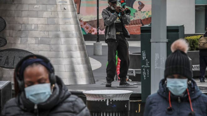 """A familiar resident of Harlem who goes by the name New World Warrior, center, plays """"Lift Every Voice And Sing"""" on his trumpet at one of multiple stops along 125th Street, blaring the song repeatedly as people walk on by Saturday April 18, 2020, in New York. """"I am not concerned about corona[virus],"""" he said, """"I am concerned about the core of racism."""" On Friday, the Centers for Disease Control and Prevention released its first breakdown of COVID-19 case data by race, showing that 30% of patients whose race was known were black. The federal data was missing racial information for 75% of all cases, however, and did not include any demographic breakdown of deaths."""