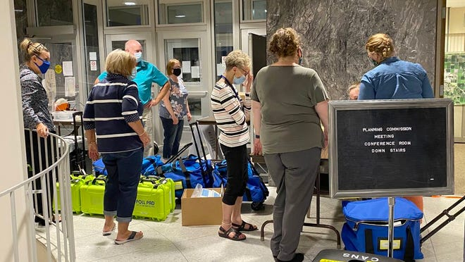 Election workers from Crookston wait to turn in their equipment