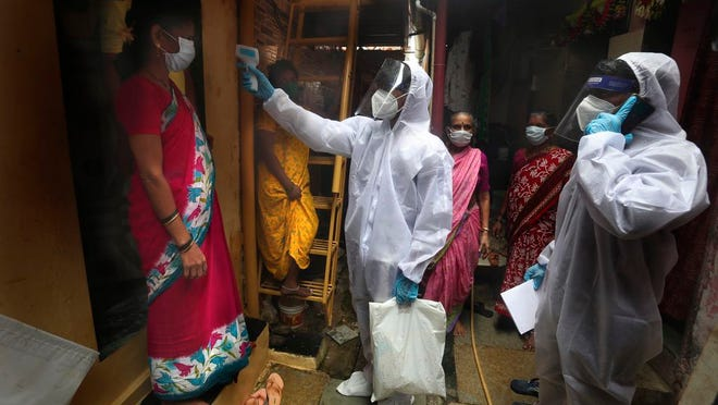 A health worker checks the body temperature of a resident, as others await their turn during a free medical checkup in a slum in Mumbai, India, Sunday, June 28, 2020. India is the fourth hardest-hit country by the COVID-19 pandemic in the world after the U.S., Russia and Brazil.