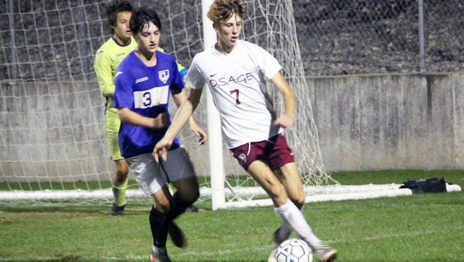 Osage senior Anthony Alberti possesses the ball in front of Camdenton's goal with Camdenton senior Tyler Banuelos in pursuit on Thursday, October 22, in Camdenton. Alberti scored two goals for the Indians.