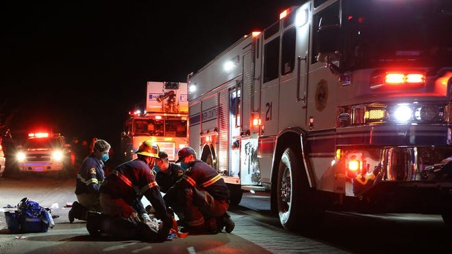 Firefighters treat man critically injured in traffic accident Thursday. He was later flown from the scene to Kern Medical