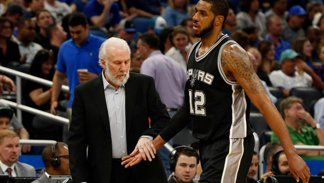 San Antonio Spurs head coach Gregg Popovich (L) high fives forward LaMarcus Aldridge (12) against the Orlando Magic during the second half at Amway Center. The Spurs won 107-79.