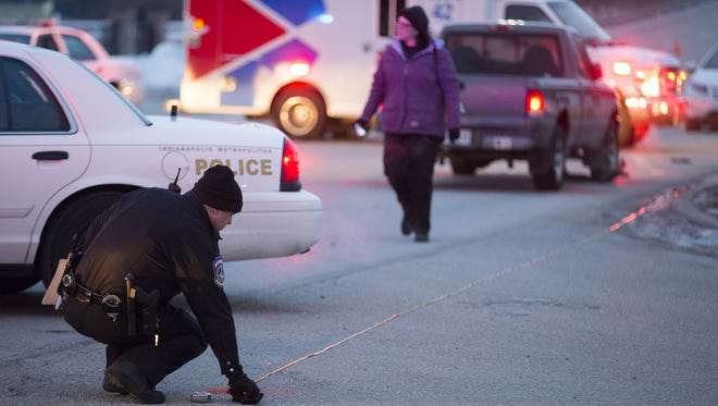 An IMPD officer makes measurements after a fatal pedestrian accident at the intersection of Brookville Road and South Kitley Avenue, Thursday, March 5, 2015. The pickup truck in the background struck a single pedestrian at approximately 5:30 am.