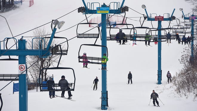 People ride a ski lift to the top of a hill Wednesday at Powder Ridge Winter Recreation Area near Kimball. Powder Ridge plans to join other ski areas nationwide in an attempt to break a world record for the largest simultaneous ski lesson.