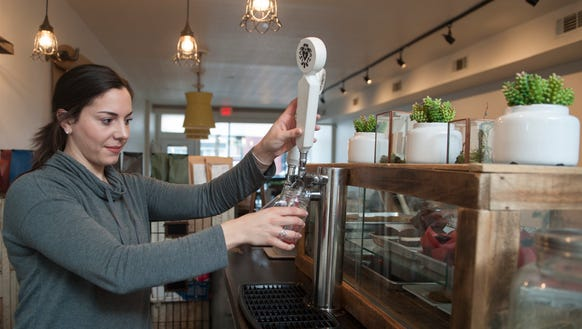 Kelsey Coyne pours an orange hibiscus kombucha at Heart