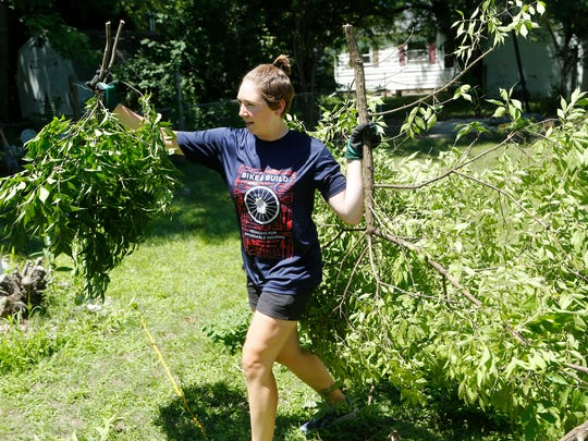 Sarah Udelhofen helps clear shrubs from the yard as