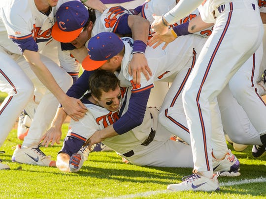 Clemson's Drew Wharton (bottom)  is swarmed by teammates in the celebration of his game winning hit in the bottom of the 9th inning against South Carolina on Sunday in Clemson's Doug Kingsmore Stadium.