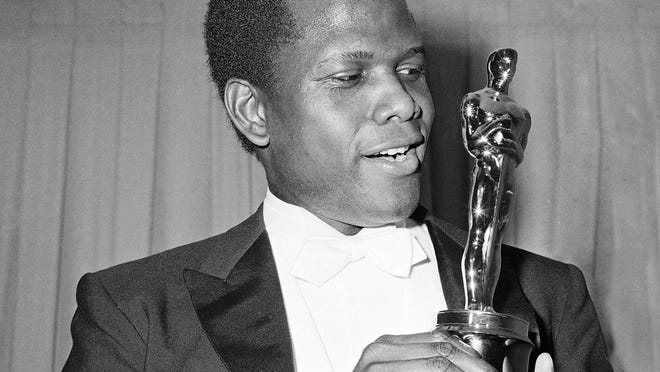 "Actor Sidney Poitier is photographed with his Oscar statuette at the 36th Annual Academy Awards in Santa Monica, Calif., on April 13, 1964. He won Best Actor for his role in ""Lilies of the Field."""