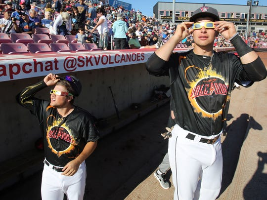 Salem-Keizer Volcanoes' players Michael Sexton, left, and Robert Calabrese look at the sun during the eclipse on Monday, August 21, 2017 at Volcanoes Stadium in Keizer, Oregon.  The Volcanoes played the Hillsboro Hops during the eclipse with a break about 10 minutes before totality.