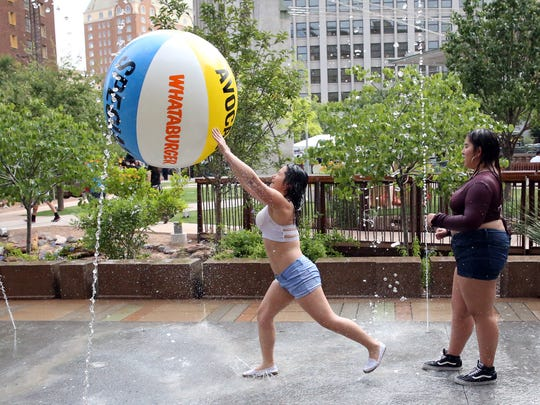 Alejandra Hernandez hits a large beach ball while playing volleyball inside the splach pad at San Jacinto Plaza on Saturday.