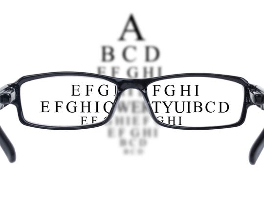 Sight test seen through eye glasses, white background