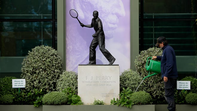 A gardener waters the plants alongside a statue of former Wimbledon Champion Fred Perry at the All England Lawn Tennis Club in Wimbledon in London, Monday, June 29, 2020. The 2020 Wimbledon Tennis Championships, that were due to start today but have been cancelled due to the Coronavirus pandemic.