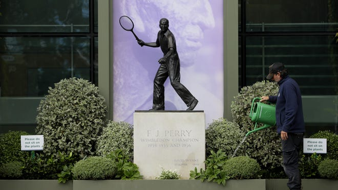 A gardener waters the plants alongside a statue of former Wimbledon Champion Fred Perry at the All England Lawn Tennis Club in Wimbledon in London, Monday, June 29.  The 2020 Wimbledon Tennis Championships, that were due to start Monday but have been canceled due to the Coronavirus pandemic.