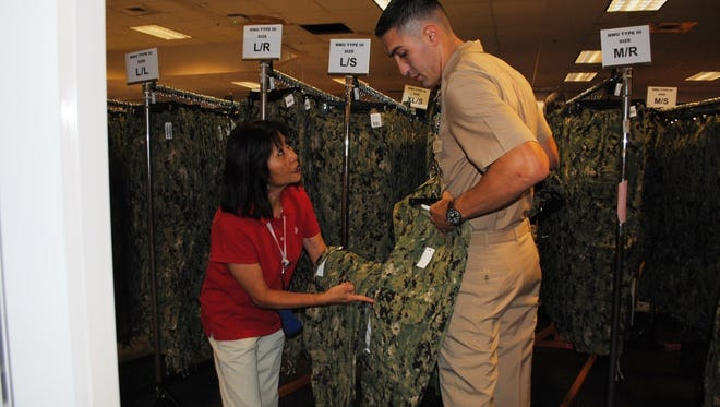 At left, Sunshine Stephens, an employee of a Pensacola Navy Exchange store, talks to a sailor about the Navy's new working uniform.