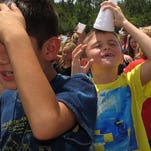 Blue Angels Elementary Principal Karen Montgomery is all smiles as she watches her students scoop up cups full of ice and pour them over their heads Friday afternoon as part of the ALS bucket challenge taken up by students and staff of the school.