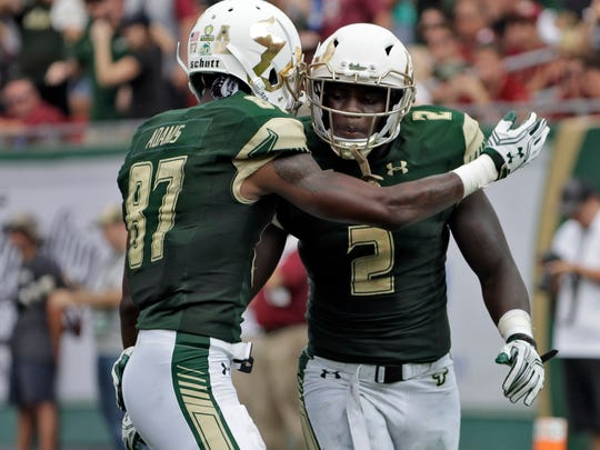 South Florida running back D'Ernest Johnson (2) celebrates with Rodney Adams (87) after Johnson's touchdown run against Florida State during the fourth quarter of an NCAA college football game Saturday, Sept. 24, 2016, in Tampa, Fla. Johnson ran for three scores in South Florida's 55-35 loss to Florida State. (AP Photo/Chris O'Meara)