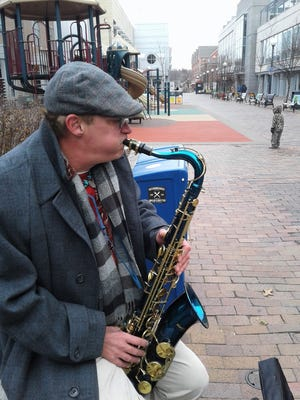 Edmund Raines blows a mournful sax while busking on the pedestrian mall in Iowa City on a chilly December day before Christmas. He's changing his lifestyle with the help of Shelter House resources.