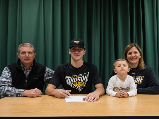 Andrew Smith poses for a photo with his parents Matt
