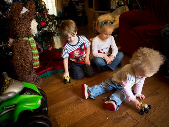 Children John, Evelyn and Violet Bell play with toys at home on Nov. 27.