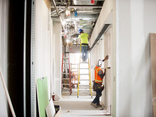 Construction workers work in a hallway that will contain