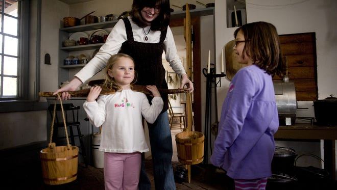 Whitall House Museum curator Megan Giordano shows some Colonial artifacts to young visitors.