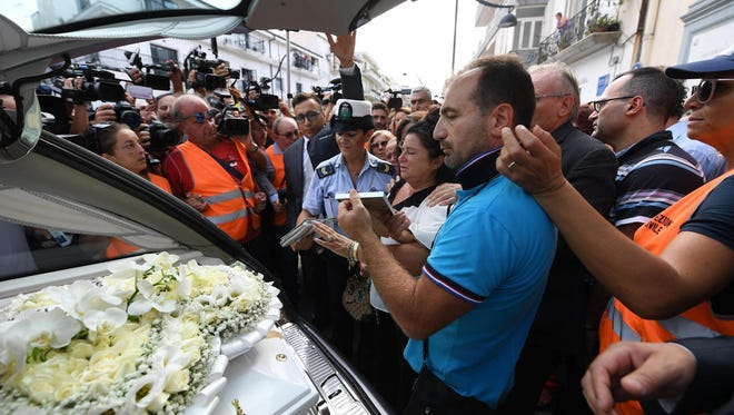 Members of the media crowd around the hearse of Tiziana Cantone as her mother Teresa Giglio, center, salutes it, during her funeral in Casalnuovo, near Naples, Italy, on Sept. 15, 2016.