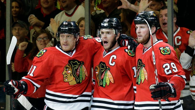 Chicago Blackhawks' Jonathan Toews, center, celebrates with Marian Hossa, left, and Bryan Bickell after scoring his goal against the Los Angeles Kings during the third period of Game 1 of the Western Conference finals in the NHL hockey Stanley Cup playoffs in Chicago on May 18, 2014. The Blackhawks won 3-1.