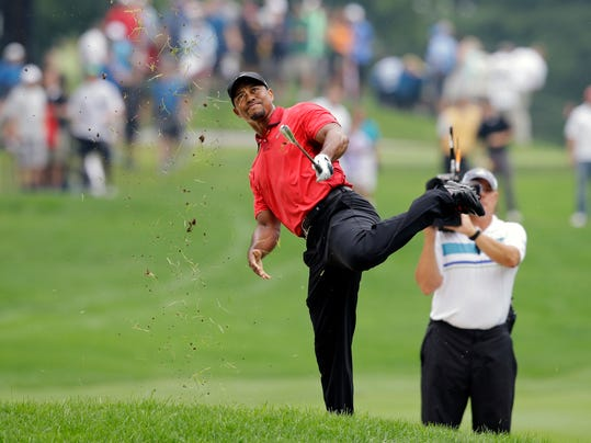 Tiger Woods makes an awkward follow through after hitting from the lip of a fairway bunker on the second hole during the final round of the Bridgestone Invitational golf tournament Sunday, Aug. 3, 2014, at Firestone Country Club in Akron, Ohio. (AP Photo/Mark Duncan)