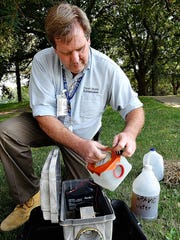 Penn State Extension West Nile Virus Program administrator Thomas Smith demonstrates the trap used to collect mosquitoes for research. A mix of straw, sour milk and tap water are fermented for a week before being used to lure mosquitoes to the trap, where they are sucked in by a fan, frozen and studied. Dawn J. Sagert photo.