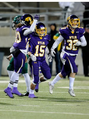 Wylie cornerback Gatlin Martin (15) is congratulated by teammates after an interception in the fourth quarter of the Bulldogs' 21-13 win in the Class 4A Div. I state semifinal playoff on Friday, Dec. 9, 2016, at Birdville Fine Arts/Athletics Complex.
