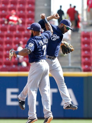 Brewers first baseman Eric Thames and second baseman Jonathan Villar react after the Brewers defeated the Reds, 4-2, at Great American Ball Park.