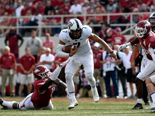 FILE - In this Sept. 9, 2017, file photo, TCU quarterback Kenny Hill (7) shakes off Arkansas defender De' Jon Harris as he scrambles out of the pocket during the second half of an NCAA college football game in Fayetteville, Ark. Hill and West Virginia's Will Grier took similar paths to the Big 12, and their head-to-head matchup is the only game Saturday matching two Top 25 teams. (AP Photo/Michael Woods, File)