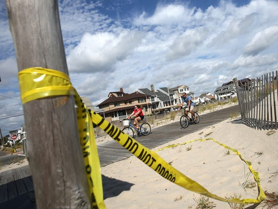 Police tape remains alongside the boardwalk near the