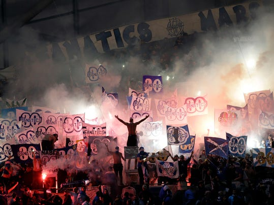 Marseille soccer supporters burn flares and hold flags during the League One soccer match between Marseille and Montpellier at the Velodrome stadium, in Marseille, southern France, Sunday, April 8, 2018. (AP Photo/Claude Paris)