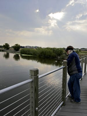 Sandy Roberts of Neenah fishes off a trestle bridge near Arrowhead Park at the south end of Little Lake Butte des Morts.