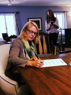 Warren Wilson College president Lynn Morton signs the Higher Education Carbon Pricing Endorsement Initiative, which urges lawmakers to support legislation that puts a price on carbon emissions and to transition to a clean-energy economy.