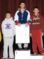 Thomas Gilman (center) and Cory Clark (left) take spots on the medal podium after the Iowa state AAU tournament in 2008.